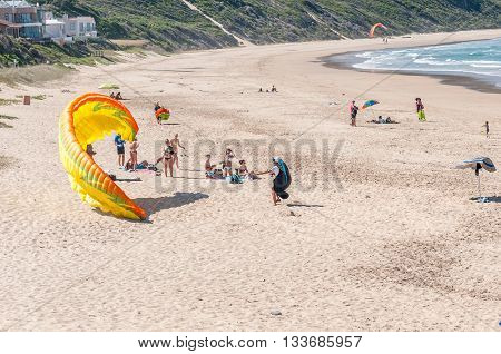 KNYSNA SOUTH AFRICA - MARCH 3 2016: A paraglider trying to get airborne while unidentified beachgoers watch at a beach in Buffelsbaai (Buffalo Bay) a small town in the Knysna municipal area