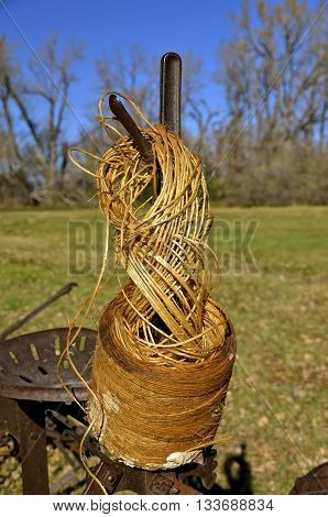 Hanging from a lever on an antique binder is roll of twine for securing the bundles of grain.