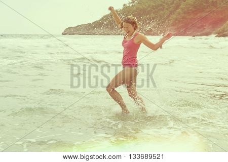 Young happy woman running through water and splashing it. Enjoyment and freedom on beach holidays