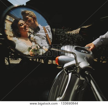 bride and groom posing on a vintage motor scooter