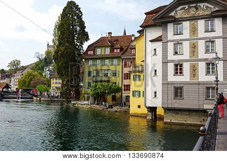LUCERNE SWITZERLAND - MAY 02 2016: Colorful buildings along the river Reuss shows unique character of the city that offers variety of tourist attractions both from history and from modern times