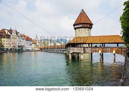 LUCERNE SWITZERLAND - MAY 02 2016: The Chapel Bridge (Kapellbruecke) together with the octagonal tall tower (Wasserturm) it is one of the Lucerne's most famous tourists attraction