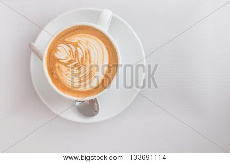 Cup of flat white coffee with milk foam pattern on a white wooden surface. Top view.