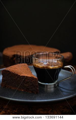 A slice of flourless olive oil chocolate cake with a cup of hot coffee on a black plate