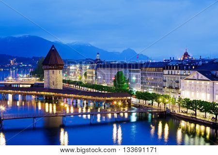 LUCERNE SWITZERLAND - MAY 03 2016: Night view towards Chapel Bridge (Kapellbruecke) together with the octagonal tall tower (Wasserturm) it is one of the Lucerne's most famous tourists attraction