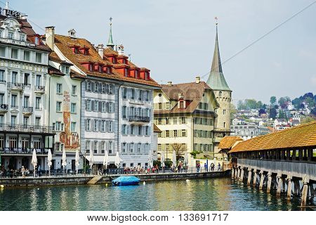 LUCERNE SWITZERLAND - MAY 02 2016: Colorful buildings of the city along river Reuss shows its unique character and variety of sightseeing attractions. The town is a destination for many travelers