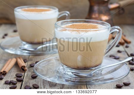 Coffee latte with cinnamon in glass cups on a wooden table