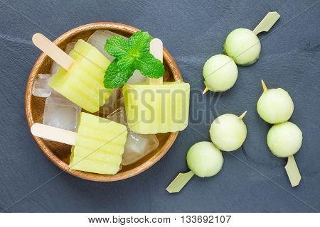 Homemade melon popsicles on a grey slate