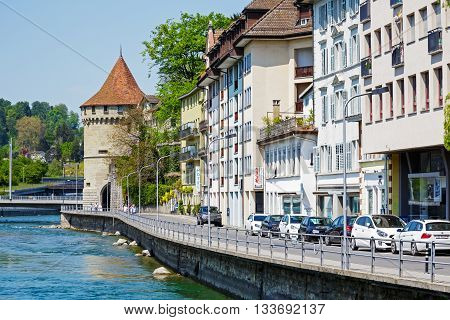 LUCERNE SWITZERLAND - MAY 08 2016: Located by the river Reuss a round tower Nolliturn is seen at the end of townhouses row. The Tower it is a part of Lucerne's ancient city walls
