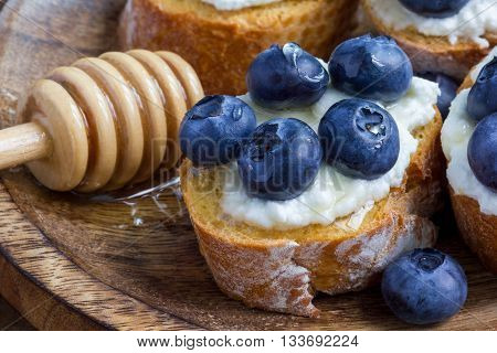 Crostini with ricotta cheese blueberries and honey on wooden plate
