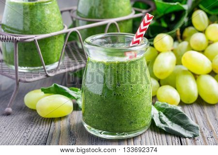 Healthy green smoothie with spinach grape and banana on wooden table
