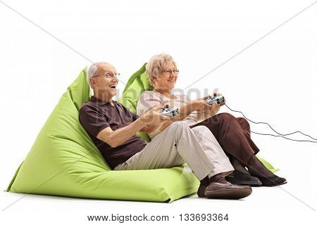 Elderly couple playing video games seated on green beanbags isolated on white background