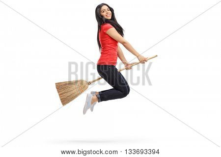 Studio profile shot of a young woman flying on a broom isolated on white background