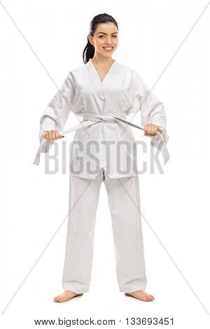 Full length portrait of a young woman in a white kimono tying her belt isolated on white background