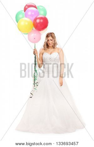 Full length portrait of a sad young bride holding a bunch of balloons isolated on white background