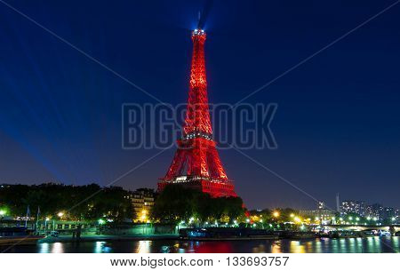 paris; France-June 09 2016 : The Eiffel tower lit up in red color for opening of soccer Europe championship 2016 in France. The Eiffel tower is on of the most visited monuments in the world.