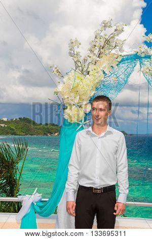 Wedding ceremony on a tropical beach in blue.The groom waits for the bride under the arch decorated with flowers on the on hotel tropical sea in the background.