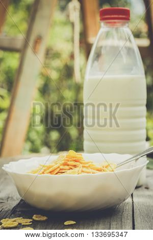 bottle of milk and bowl of cornflakes on the table