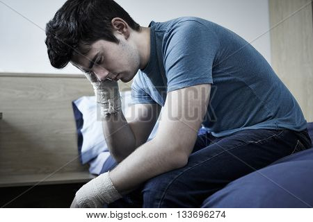 Depressed Young Man With Bandaged Wrists After Suicide Attempt