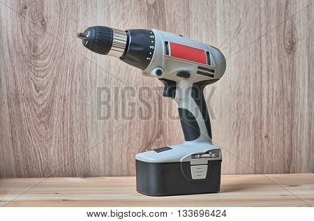 Battery screwdriver or drill on wooden background close up.
