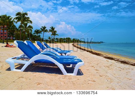 May 20, 2016 in Key West, FL:  Lounge chairs where tourists can relax with sunbathers on the sand beyond taken at a white sand beach called Smathers Beach taken in Key West, FL