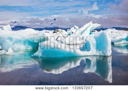 Ice splendor. Iceland. Floating ice and clouds reflected in the mirror-smooth water lagoon Ice