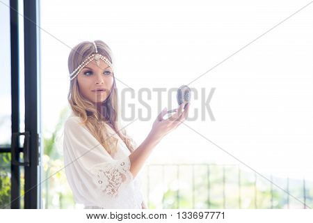 beautiful young bride in a white dress with the mirror. Last preparations for the wedding. Bride waits for her groom. Morning the bride.