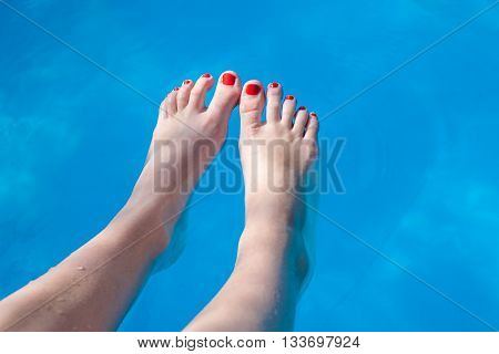 Young girl legs soaking in the water pool