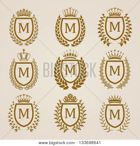 Set of luxury golden shields with laurel wreaths, crowns. Royal heraldic elements, emblems, icons, symbols, labels, badges, blazons, monograms for web, page design. Vector illustration EPS 8