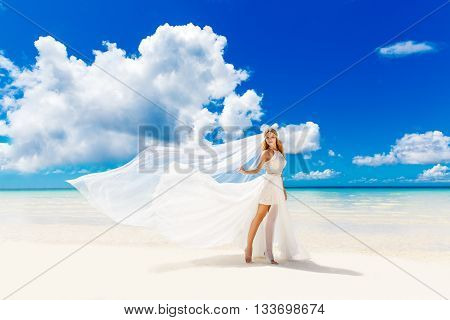 Beautiful blond bride in white wedding dress with big long white veil stand on shore sea. Tropical sea in the background. Summer vacation concept.