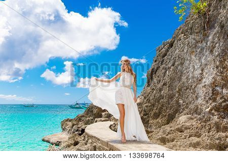 Beautiful bride on the rock. Turquoise sea in the background. Wedding and honeymoon in tropics concept.