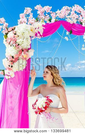 Wedding ceremony on a tropical beach in purple. Happy blond bride with wedding bouquet under the arch decorated with flowers on the tropical sand beach. Wedding and honeymoon concept.