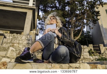Beautiful blonde girl with curly hair is seating on the steps with tablet in hands and watching into the distance.