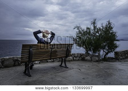 Girl is seating on the bench near of the sea and looking into the distance