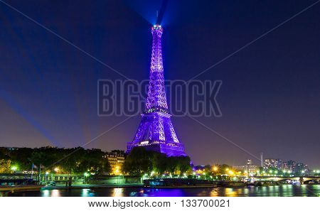 paris; France-June 09 2016 : The Eiffel tower lit up in purple color for opening of soccer Europe championship 2016 in France. The Eiffel tower is on of the most visited monuments in the world.