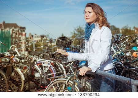 Woman with a key unlocking her bicycle at a huge bike parking in Amsterdam