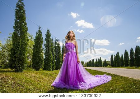 Blonde lady in violet dress with long skirt near row of green trees in sunlight