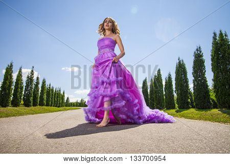 Portrait of blonde young barefoot woman in pink princess dress on alley in sunlight