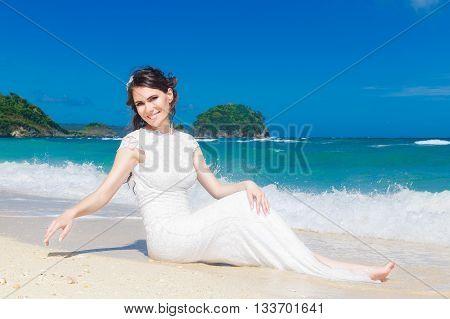 Happy bride having fun on a tropical beach. Wedding and honeymoon on the tropical island.