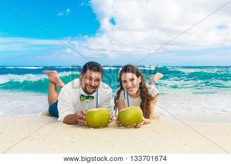 Happy bride and groom having fun on a tropical beach with coconuts. Wedding and honeymoon on the tropical island.