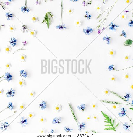 floral frame with chamomile flowers cornflowers and green branches. Flat lay top view