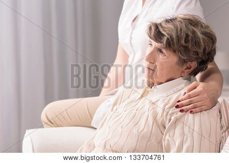Sad senior woman sitting carer holding hand on her arm.