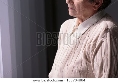 Sad senior woman standing alone in dark room.