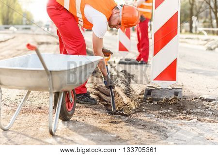 Workman loading a wheelbaroow on the construction site