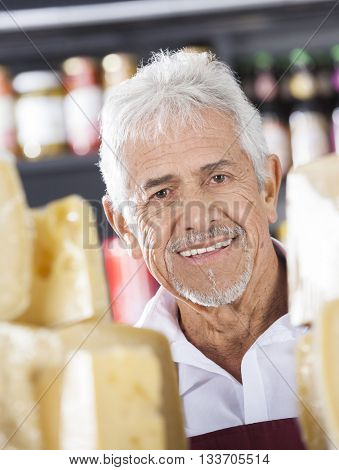 Happy Senior Salesman In Cheese Shop