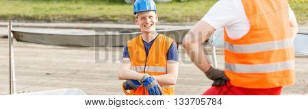 Young workman smiling to a friend on the construction site