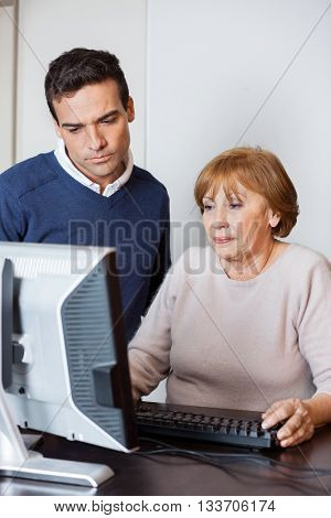 Tutor Assisting Student Using Computer In Lab
