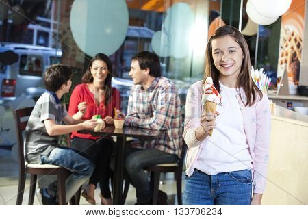 Smiling Girl Holding Vanilla Ice Cream Cone In Parlor