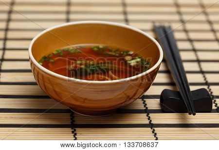 Miso soup in brown bowl standing on bamboo mat with back chopsticks lying near.
