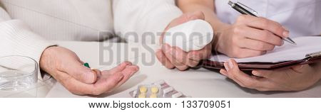 Doctor prescribing medicine pills - closeup of hands